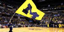 University of Michigan flag paraded on basketball court before NCAA tournament game.