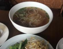 A large bowl of pho, a broth based Vietnamese soup, sit on a table filled with noodles. A plate next to this bowl holds bean sprouts and Thai basil.