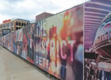 "Image of gates covered with ads regarding ""District Detroit."""