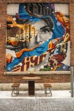 A bench sits in front of the side of a brick building, which has a very detailed mural of a woman's face, covered by layers of other paintings, bright and colorful.