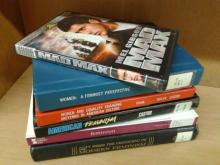 "A stack of several feminist books with a DVD copy of the film ""Mad Max"" sitting on top."