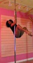 Woman in black leotard holding herself off the floor on a vertical pole.