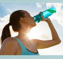 Photo of a woman drinking from a reusable water bottle.