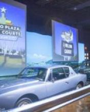 "A classic car is displayed in front of photos of roadside signs. One sign reads, ""Alamo Plaza Hotel Courts"". It is in an art deco retro style."