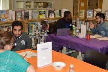 Students and staff at tables representing different backgrounds.