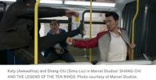 Shang Chi (Simu Lui) and Katy (Awkwafina) fighting a member of the Ten Rings on a bus.