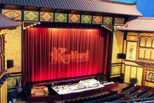 The ornate front display of the inside of the Redford Theater, which is done in a classic style that can be described as oriental. The organ can be seen in front of the stage.