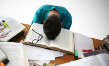 A student face palmed on his textbook and surrounded with many books and a glasses