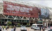 """Image shows a red banner across the TCF Center reading, """"The Cobo Center is now TCF Center. We're proud to call Detroit home."""""""