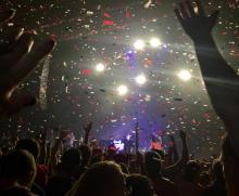 Confetti flies down from the ceiling inside a large concert hall. The crowd inside raises there hands up. Lights shine from the stage as a band plays.
