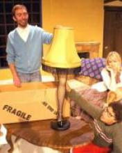 Actors Matt Van Houten, Brigid Driscoll, and Blues Higgerns sit in a staged living room and look on as Houten steadies a lamp. The lamp shade is yellow and of an older, dated style. It has a black fringe. The base of the lamp is a leg in fishnet stockings and a high-heeled shoe.