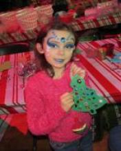 A child, Nicole, smiles at the camera as she displays a foam Christmas tree she has covered with plastic jewels. Her face has been painted and also adorned with jewels. Behind her is a crafting table covered with other seasonal art supplies.