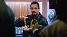 "Still image from ""Uncut Gems"" showing Adam Sandler holding a Furby gold chain"