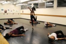 Dancers bending backward in circle around female dancer twirling on one leg in rehearsal studio.