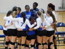 Photo of Hawks girls volleyball in team huddle with the coach on the sideline.