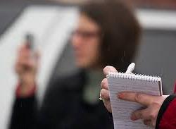 Close up of journalist writing on a notepad with blurred woman holding a mic in the background.