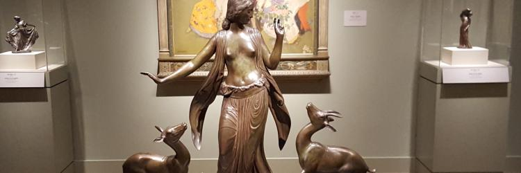 Bronze statue of woman dancing with animals.
