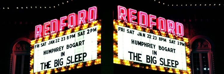"A big, bold theater marque displays, ""Redford"" in large red letters. It advertises showings of Humphrey Bogart in The Big Sleep."