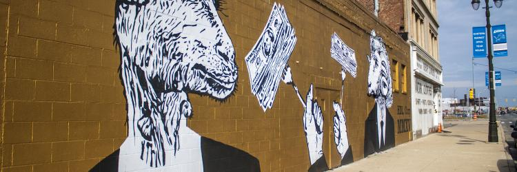 A brick building has black and white paintings of a goat and a ram in suits and ties. They have forks holding up bundles of cash.