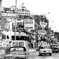 "A black and white photo captures a busy street scene, with cars from the 1950s driving past a block filled with businesses with large signs. Some of the signs read: ""Super Market"" ""Checks Cashed"" ""Standard [Oil]"" ""Williams Drugs"""