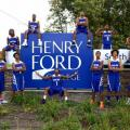 Photo of Henry Ford College Hawks mens basketball team posed around the Henry Ford College sign at the college's entrance.