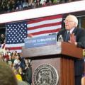Bernie Sanders speaking from a podium at Eastern Michigan University. Behind him is a large American flag and many supporters.
