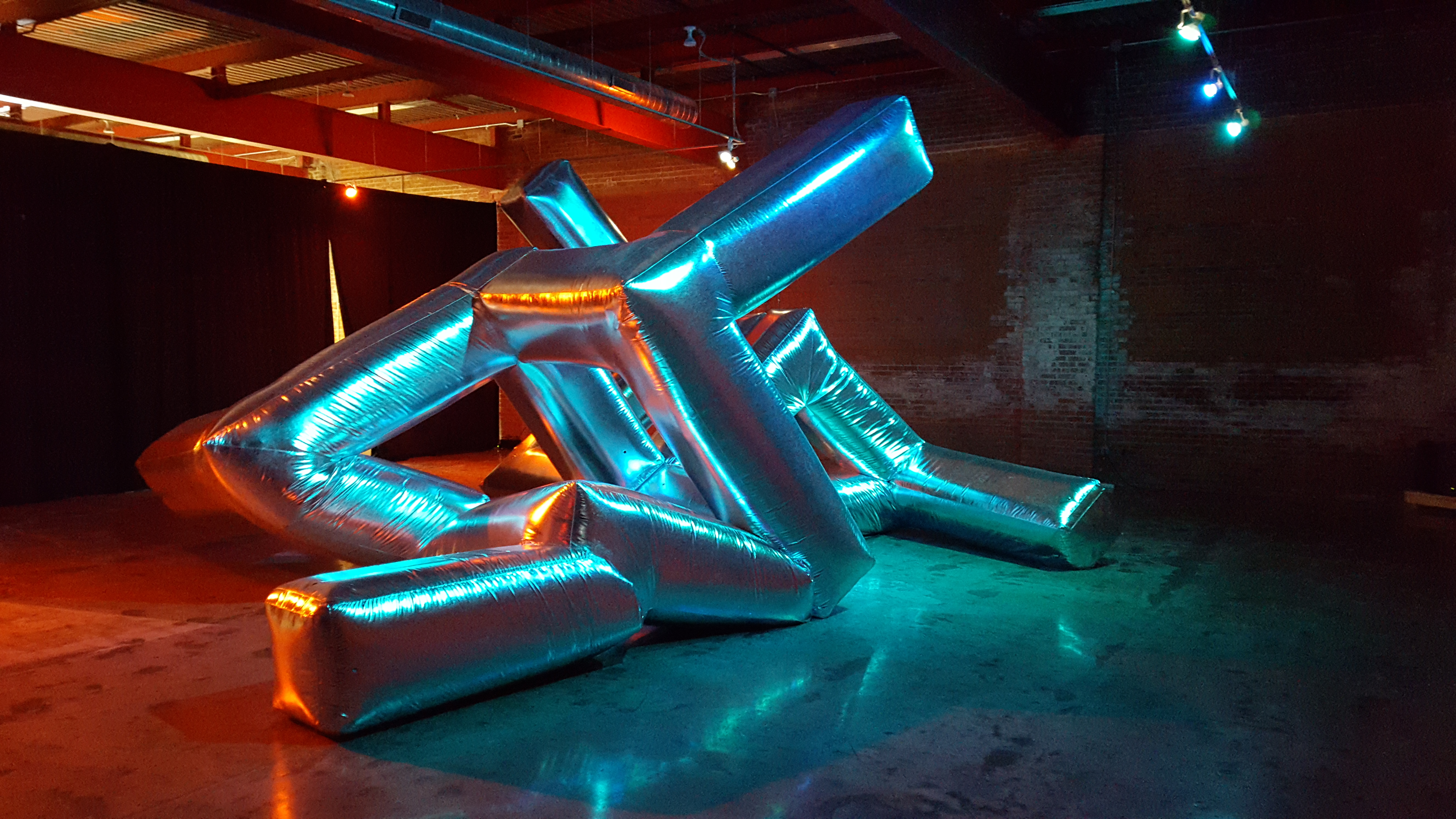 """A shiny, inflated, metallic art piece fills a room. The """"sculpture"""" is geometric, but appears to be stuffed or inflated. Several arms coming off of the piece, which bend at various points. It fills the large loft style space it is photographed in."""