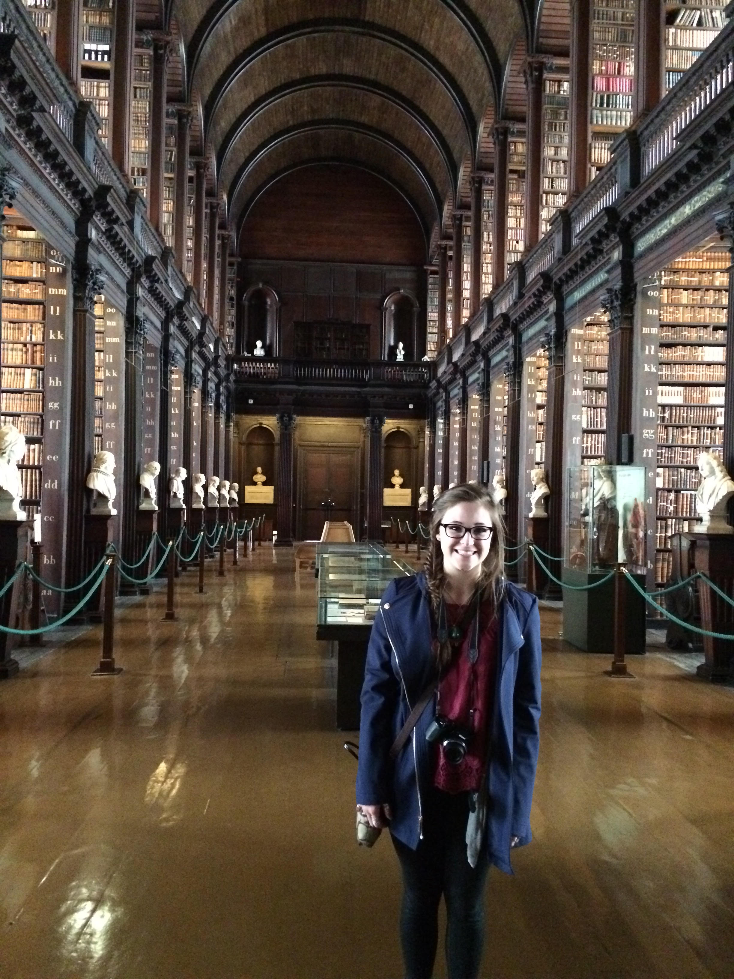 Photo of Sophia Hart standing on the main floor of the Old Library at Trinity College with its historic high vaulted ceilings.