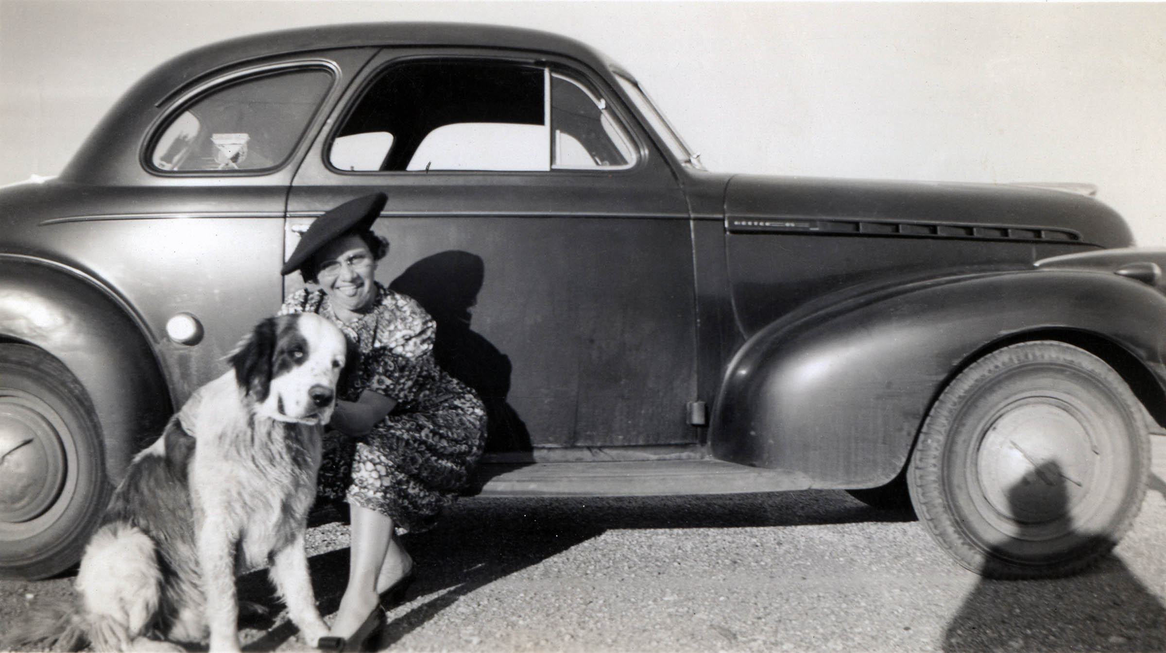 Portrait of a woman sitting on an automobile with her dog, around 1940-1950. Photographer unknown. Courtesy DIA.